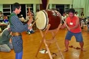 Photograph : Men are playing a Japanese traditional big drum at Bon-odori Festival.