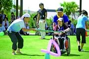 """Photograph : A pair with wheelchair man is showing the """"Universal Sports"""" that they are created."""